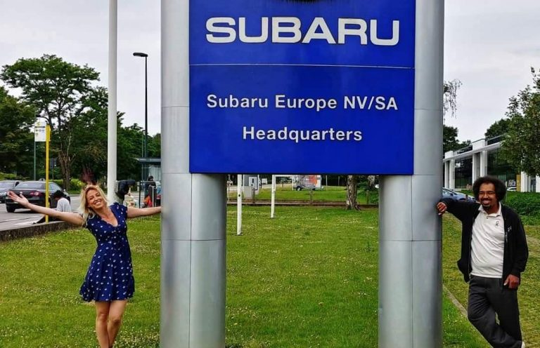 Two people standing beside a large Subaru headquarters sign outside
