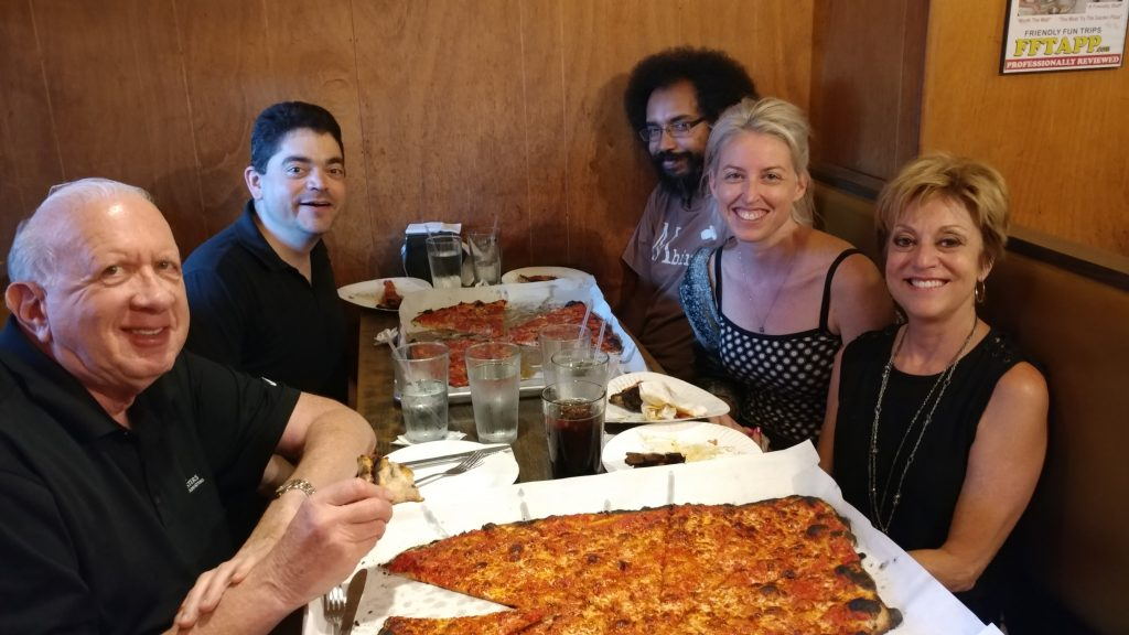 An image of 5 people sitting at a table with very large pizzas set before them.