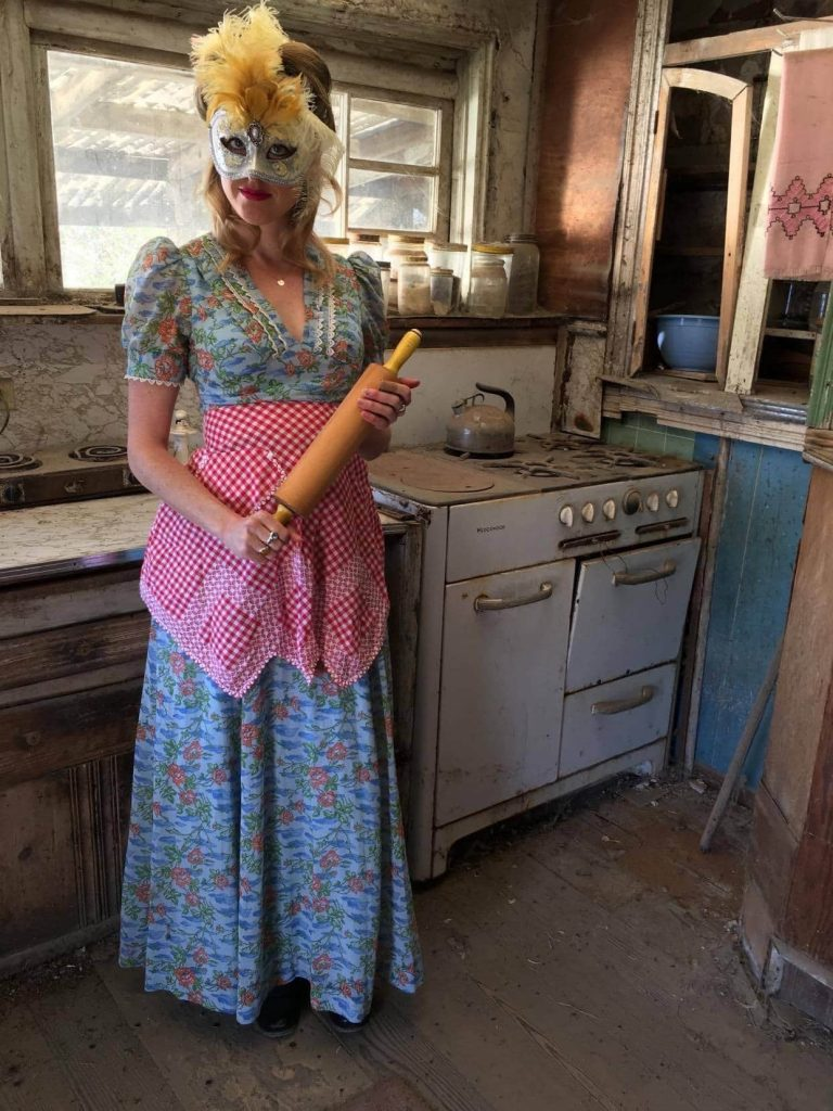 A woman in a dilapidated kitchen with a decorative mask on. She is wearing a floral print dress with a checkered apron and holding a rolling pin.