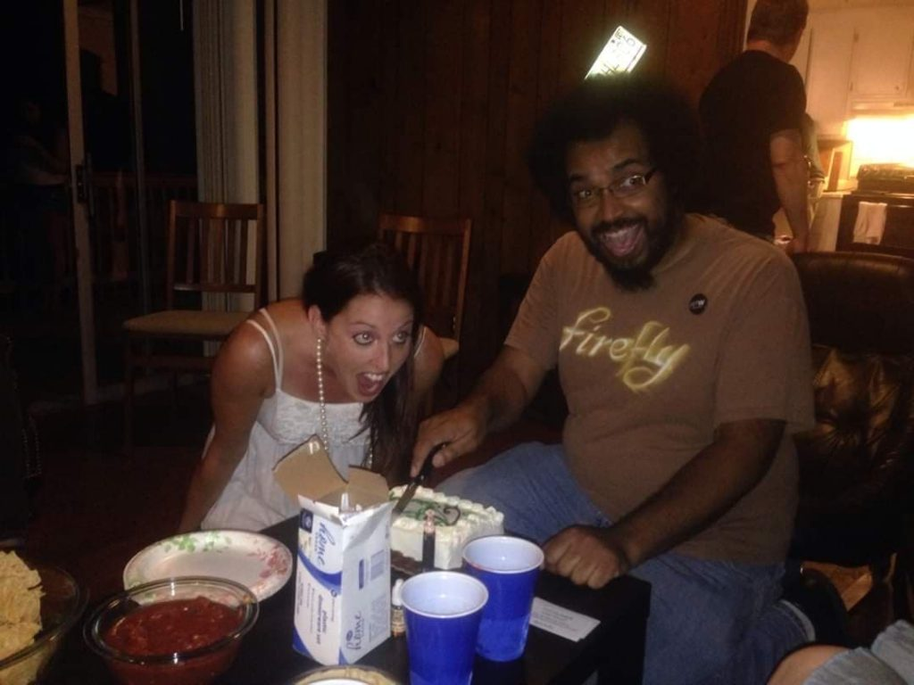 A man and a woman sitting at a table in a house in front of a cake; the woman is pretending to take a bite of the cake.