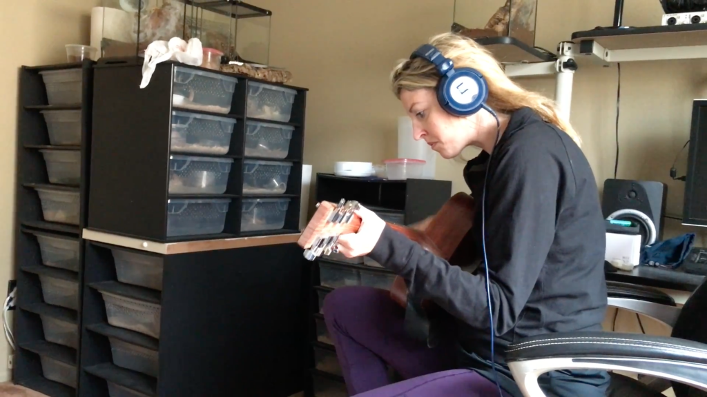 A woman sitting in a room wearing headphones and playing guitar.