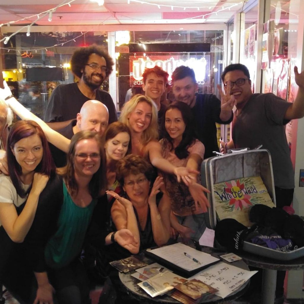 A photo of a smiling crowd standing behind a table of merchandise.