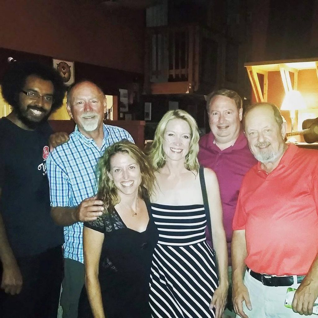 A photo of a group of people - four men and two women - standing together in a bar.