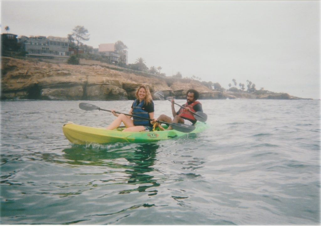 A photo of two people, a man and a woman, in a kayak on the ocean with the coast in the background.