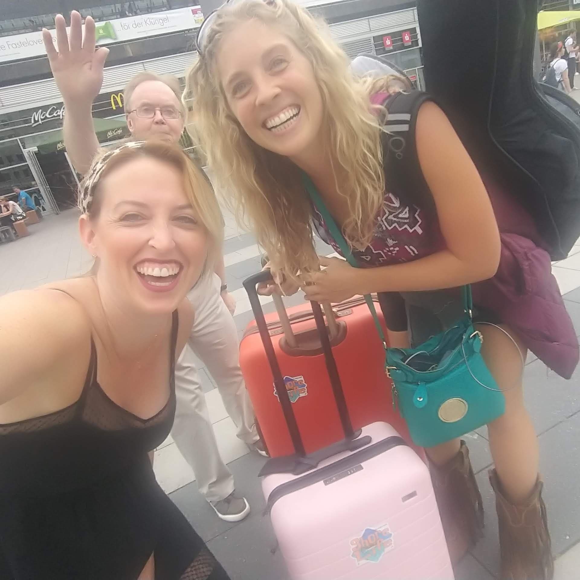 Two women smiling at the camera with a man waving in the background