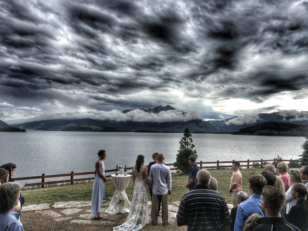 A photo of a wedding with the sky filled with silvery clouds