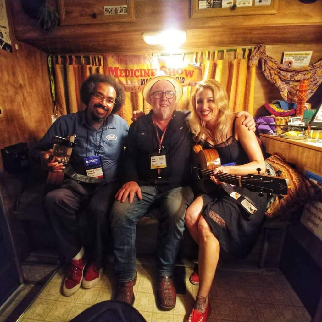Two men and one woman sitting on a couch in an RV.