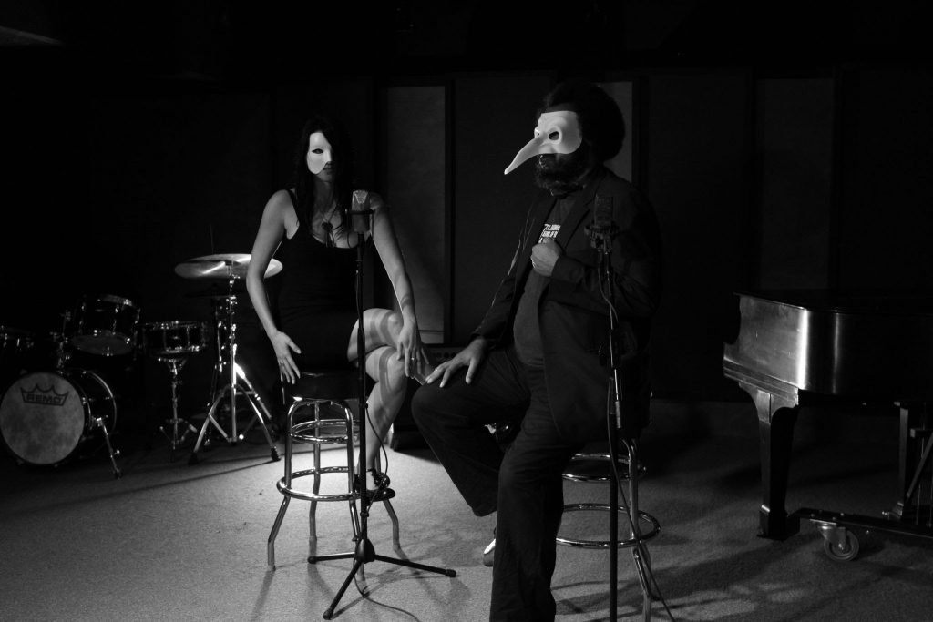 Ashley and Ed are sitting in a room with microphones, a drumset, and a piano. They are wearing haunting masks and posing as if performing.