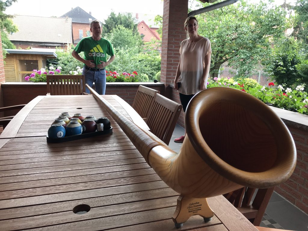 A man and a woman stand behind a genuine Alphorn set upon a table on a back porch.
