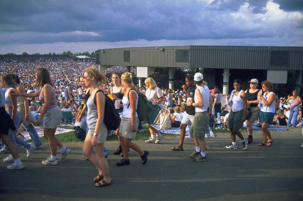 A crowd of people attending Lilith Fair walking by on a lawn in front of a building.