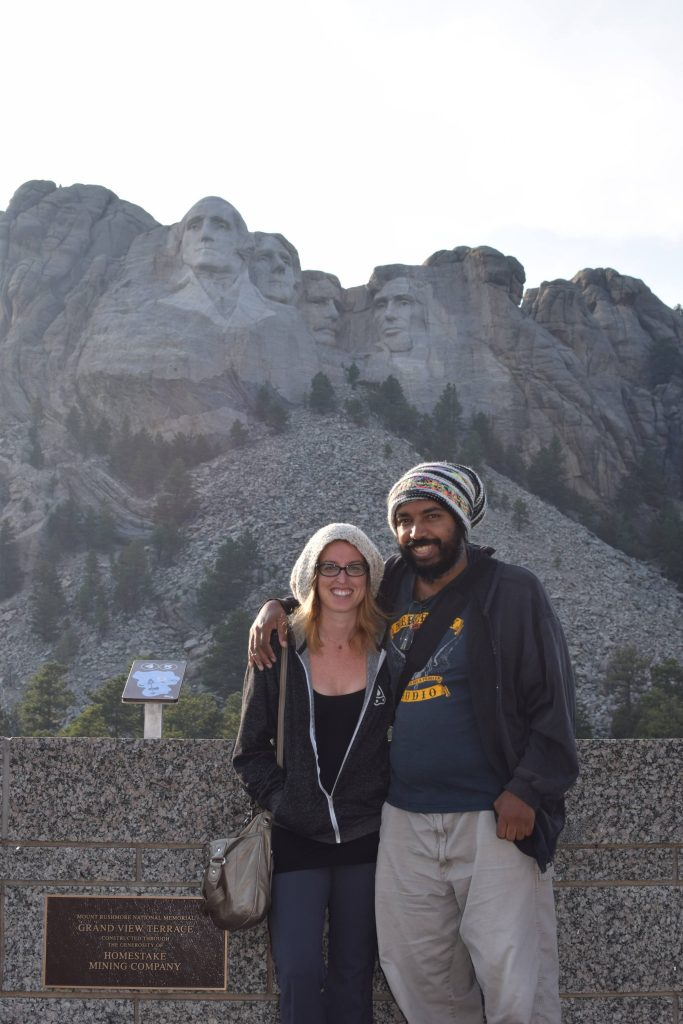 A man and woman standing in front of Mount Rushmore