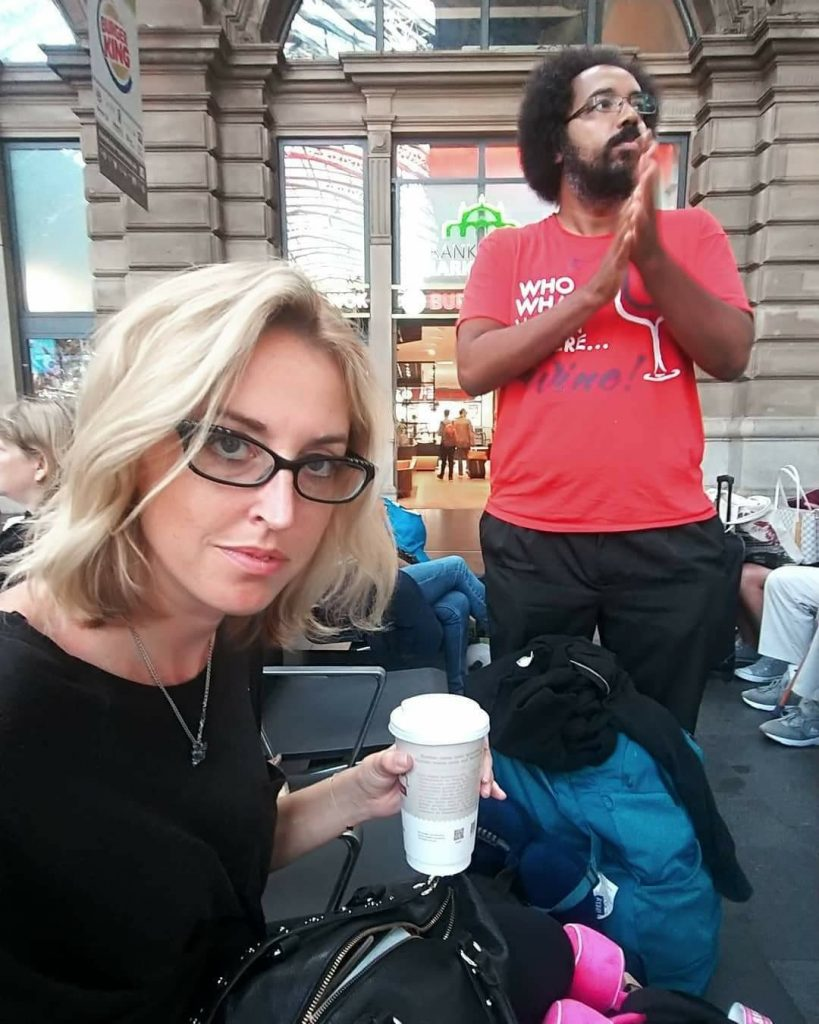 A woman with a coffee in her hand stares at the camera while a man stands and looks off in the distance expectantly.