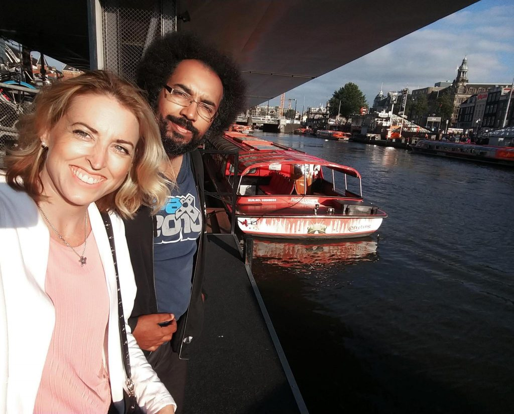 Ashley and Edward standing on the dock of a canal in front of a red tour boat.